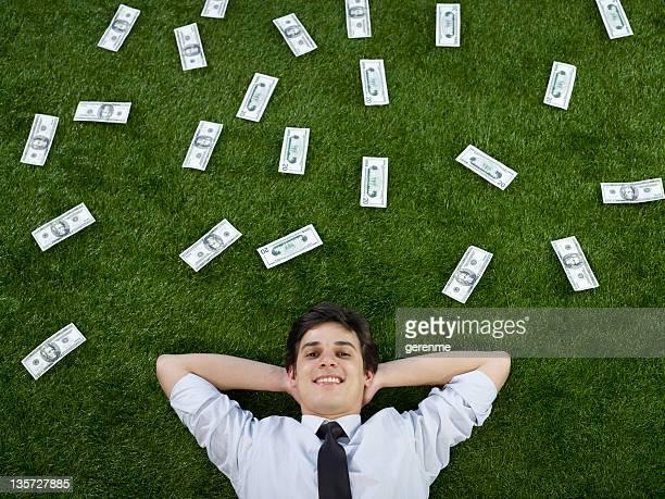 Uomo d'affari posa sull'erba con dollari