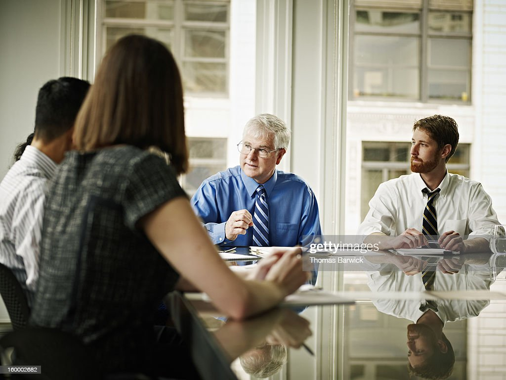 Businessman leading coworkers in discussion : Stock Photo