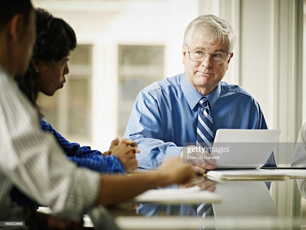 Businessman leading discussion with coworkers : Stock Photo