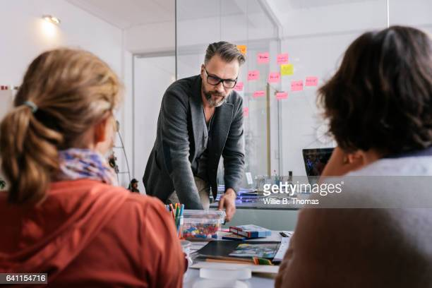 Businessman leading group working on problem
