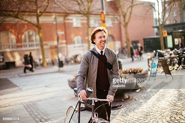 Businessman leading his bicycle through city