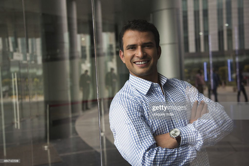 Businessman leaning against a glass wall in office : Stock Photo