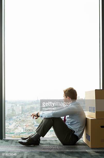 Businessman leaning against cardboard boxes looking out of window