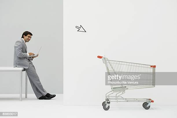Businessman leaning against desk, shopping online, cursor pointing at shopping cart