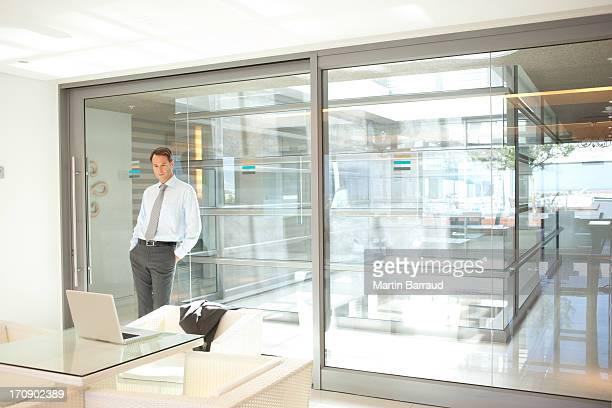 Empresário Inclinar-se contra a parede de vidro do Escritório