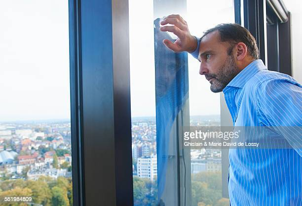 Businessman leaning against office window gazing at Brussels cityscape, Belgium
