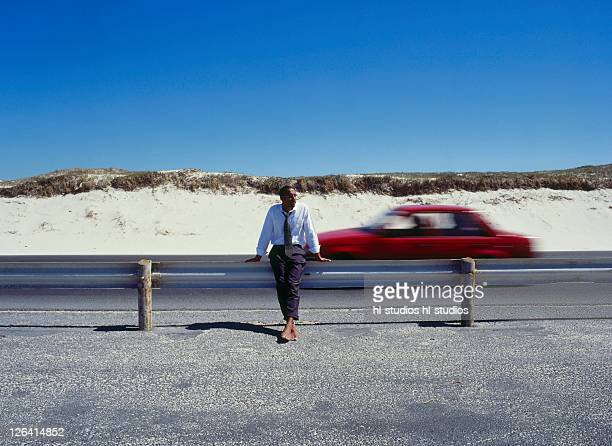 Businessman leaning against railing at roadside