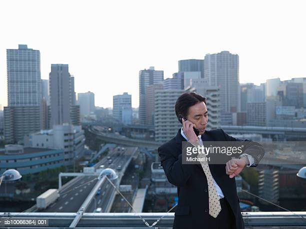 Businessman leaning against railing on roof top using mobile phone and looking at wrist watch