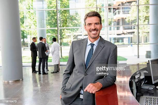 Businessman leaning against reception desk smiling widely