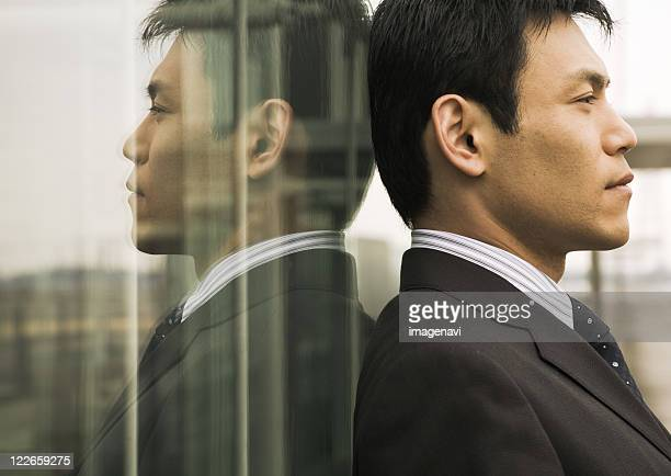 Businessman leaning against wall