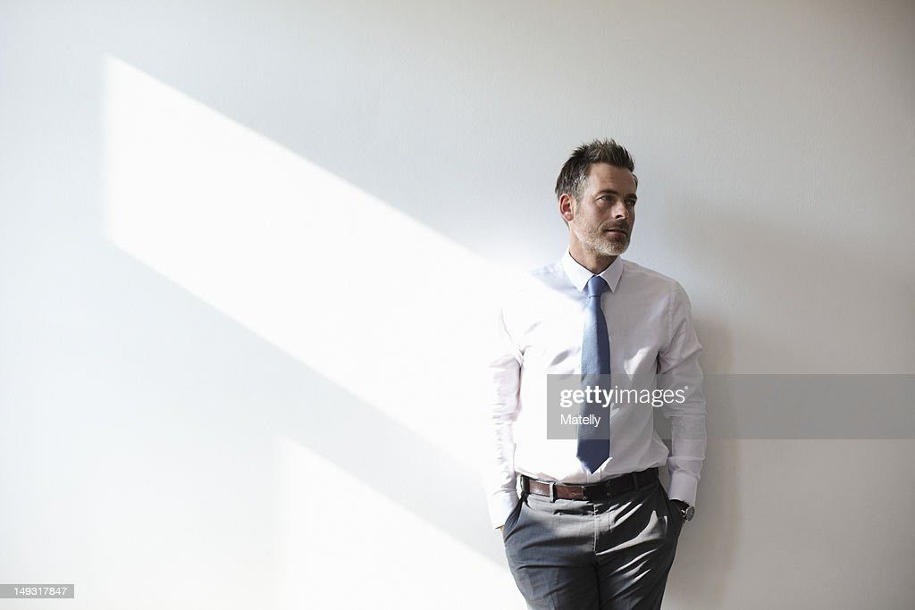 Businessman leaning against wall : Stock Photo