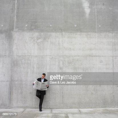 Businessman leaning against wall reading newspaper : Stock Photo