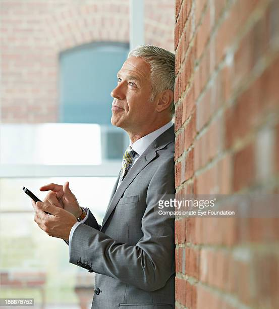 Businessman leaning against wall with mobile phone