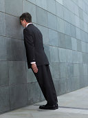 Businessman leaning forward, resting face against wall, side view