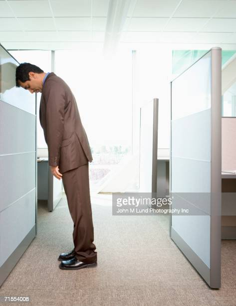 Businessman leaning head against office cubicle wall