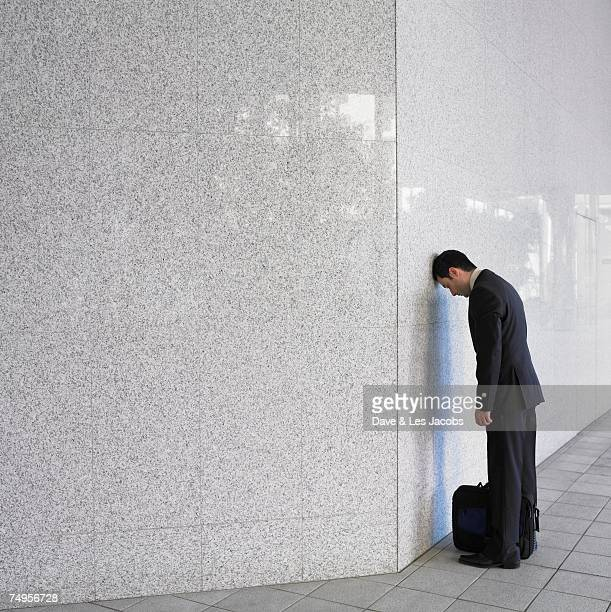Businessman leaning head on wall