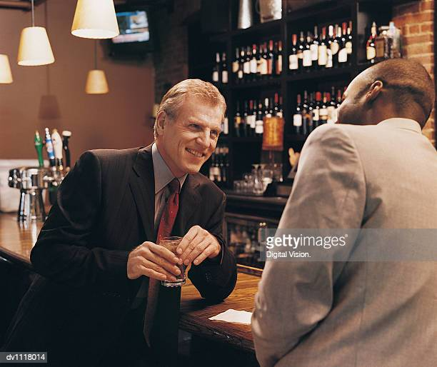 Businessman Leaning on a Bar Holding a Drink and Talking to a Colleague