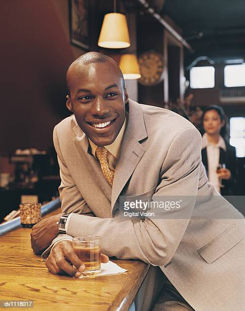Businessman Leaning on a Bar Smiling and Holding a Drink