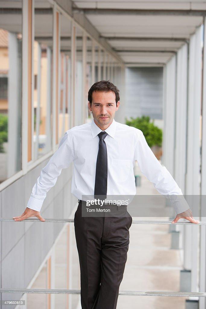 Businessman leaning on balcony railing : Stock Photo