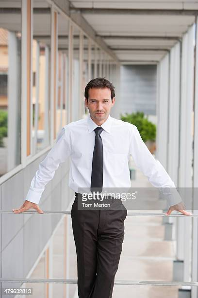 Businessman leaning on balcony railing