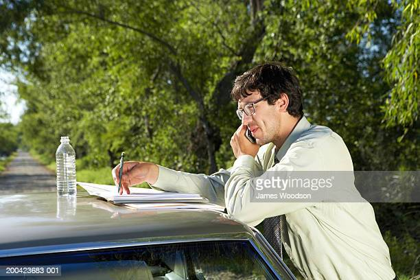 Businessman leaning on car, using cell phone, side view, close-up