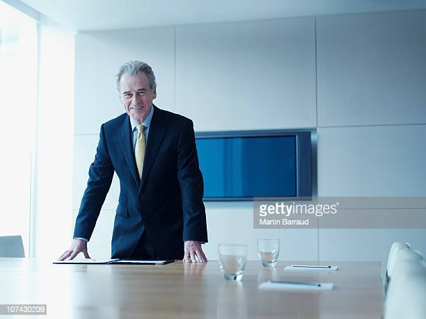 Businessman leaning on conference room table