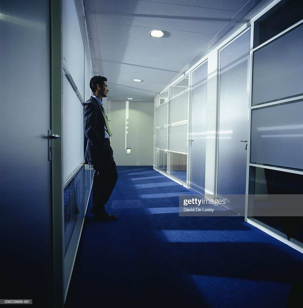 Businessman leaning on corridor wall : Stock Photo