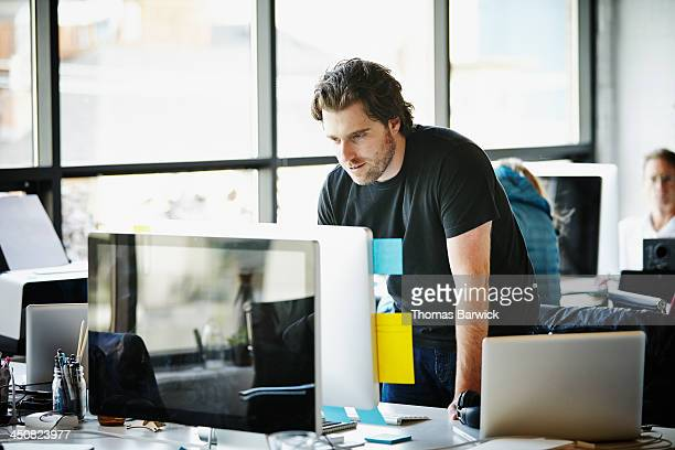 Businessman leaning on desk working on computer