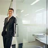 Businessman leaning on glass wall in office corridor, portrait
