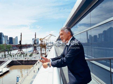 businessman leaning on railing stock photo thinkstock