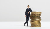 Full growth portrait of a businessman leaning on a stack of big golden coins on a white background. Earning a stable income. Feeling confident about your money. Providing revenue.