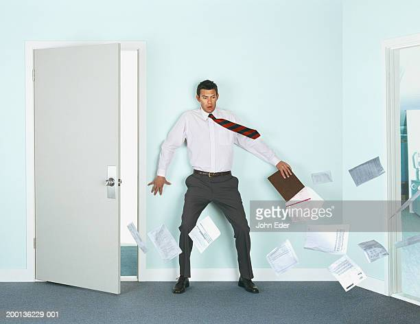 Businessman leaning on wall by doorway, tie and papers blowing in wind