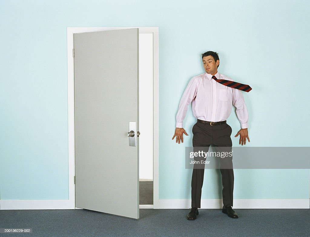 Businessman leaning on wall by doorway, tie blowing in wind