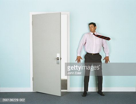 Businessman leaning on wall by doorway, tie blowing in wind : Stock Photo