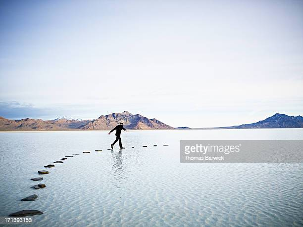 Businessman leaping between stones on pathway in l