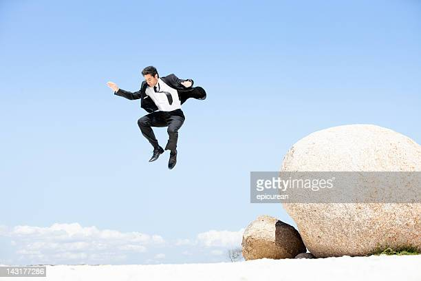 Businessman leaping off a boulder