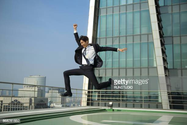 businessman leaping on urban rooftop