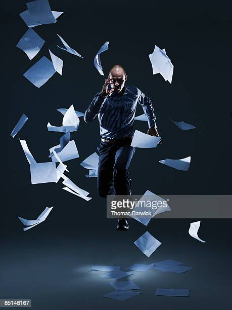 Businessman leaping through falling papers