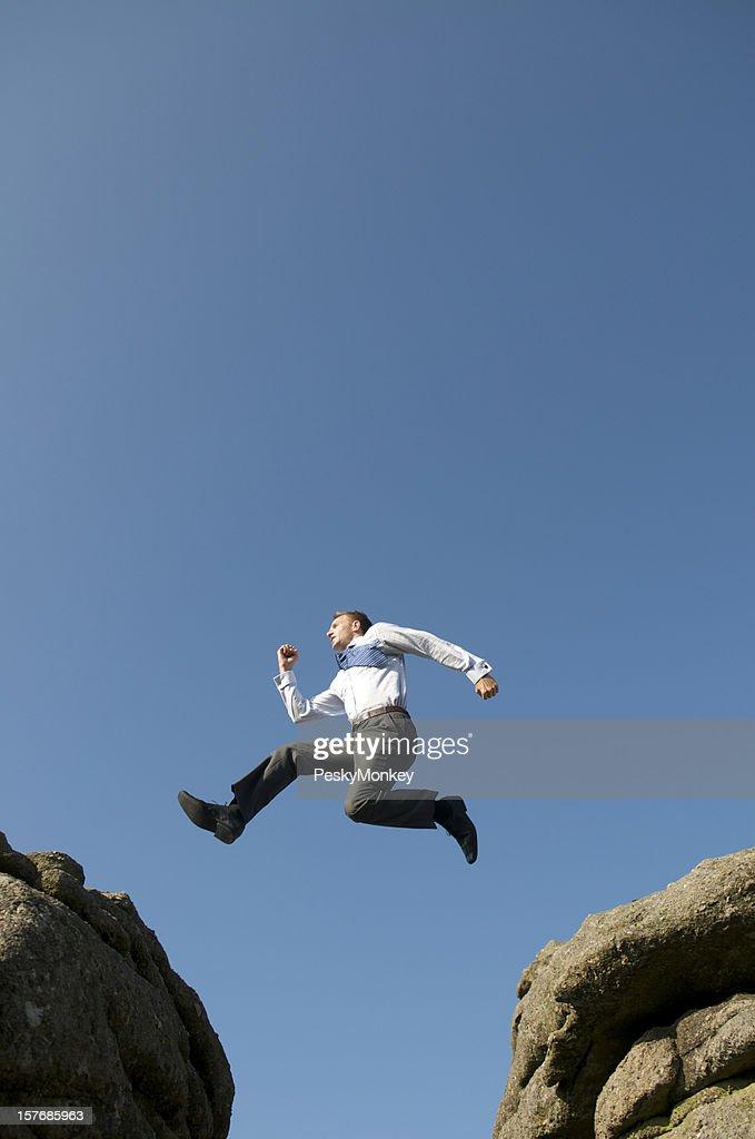 Businessman Leaps Between Big Boulders : Stock Photo