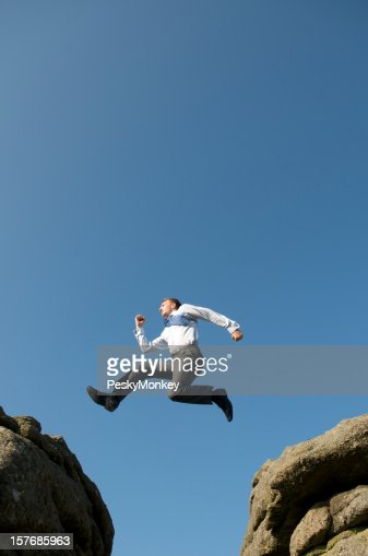 Businessman Leaps Between Big Boulders : Stock Photo