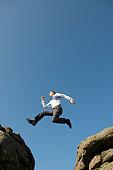 Businessman Leaps Between Big Boulders
