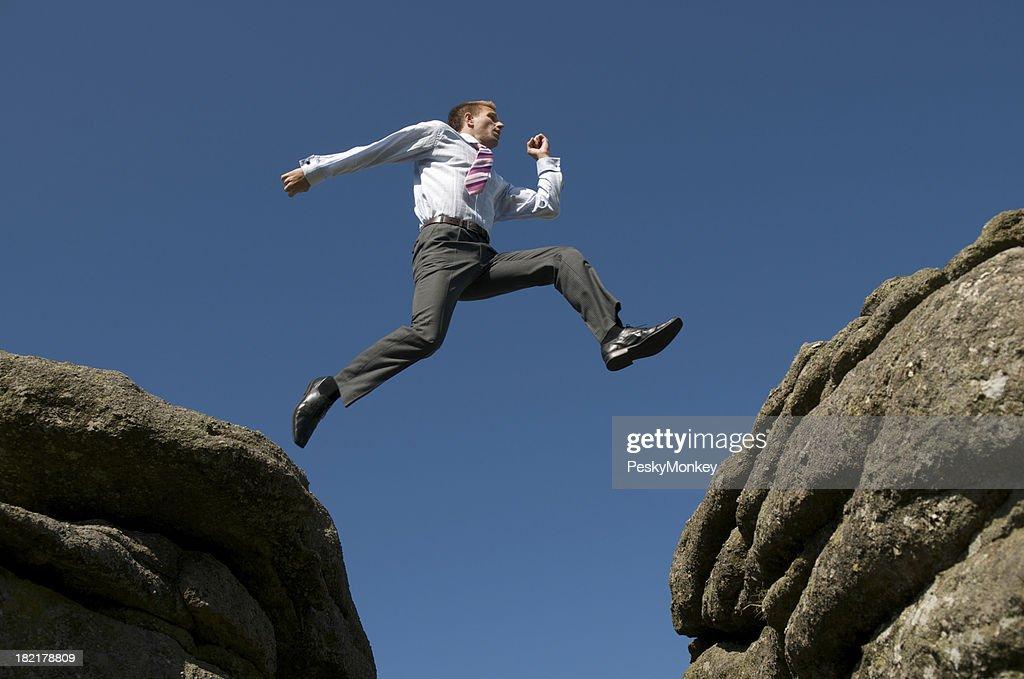 Businessman Leaps Between Rocks