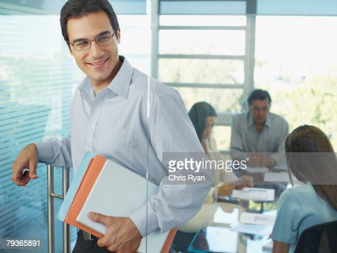 Businessman leaving boardroom with three businesspeople in background : Stock Photo