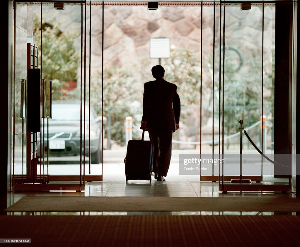 Businessman leaving lobby with luggage, rear view : Stock Photo