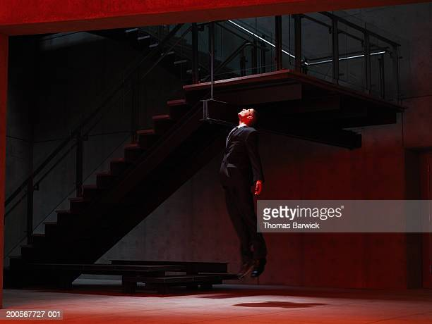 Businessman levitating in stairwell, side view