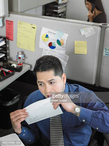 Businessman licking envelope flap, elevated view
