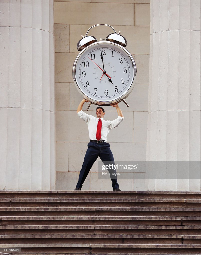 Businessman lifting alarm clock : Stock Photo