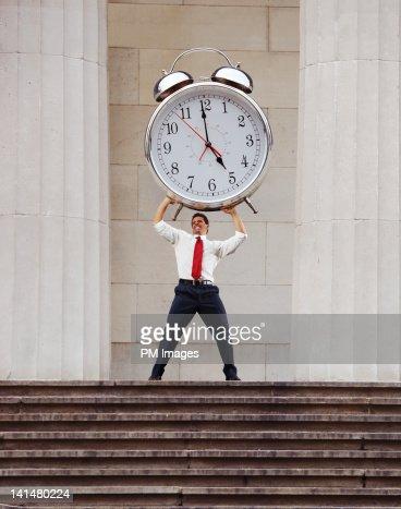 Businessman lifting alarm clock : Stock Photo