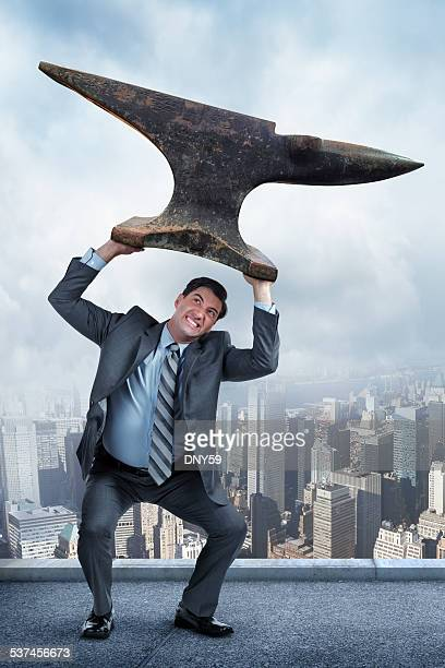 Businessman Lifting Anvil Over His Head