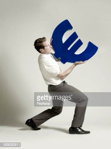 Businessman lifting large Euro symbol